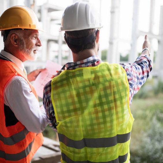 Team of architects and engineers in group on construciton site check documents and business workflow